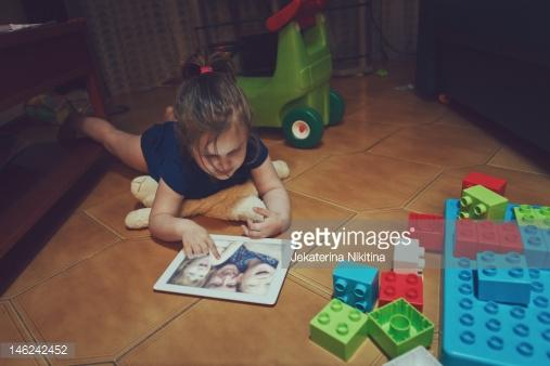 دختری که روی تبلت عکس نگاه میکند