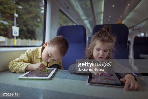 خواهر و برداری که در قطار از تبلت استفاده میکنند
