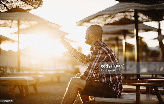 مردی که روی صندلی نشسته و با موبایل سرگرم شده است