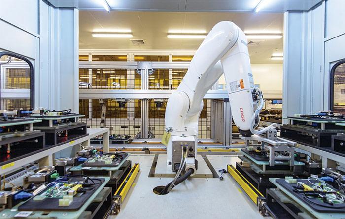 یک بازوی روباتیک بوردهای الکترونیکی را برای آزمایش در کارخانهی CIG جابجا میکند. قبلا این کار دستی انجام میشد.