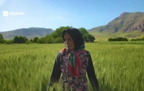 یکی از زنان روستای هرسین کرمانشاه در حال راه رفتن در زمین کشاورزی