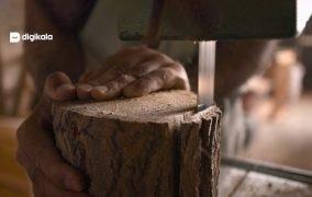 دست یک نجار در حال کار روی چوب در یک کارگاه نجاری