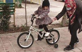 دختربچه ای درحال دوچرخه سواری در پارک