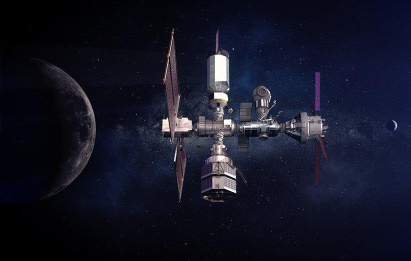 طرحی گرافیکی از ایستگاه مداری «دروازهی ماه» (Lunar Gateway) در مدار ماه و زمین که در دوردست دیده میشود.
