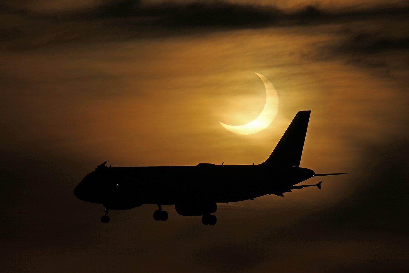 پرواز یک هواپیما از کنار منظرهی نخستین خورشیدگرفتگی 2021